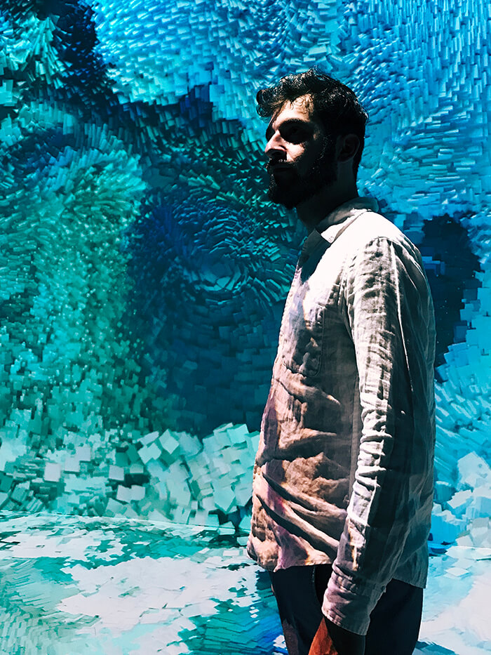 Hayk Mikayelyan in a white shirt standing in front of an immersive artwork